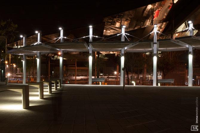 Fotografia nocturna de la plaça del davant dels Encants on l'arquitectura geomètirca contrasta amb l'orgènica de l'edifici. ©Imma Mestre Cunillera