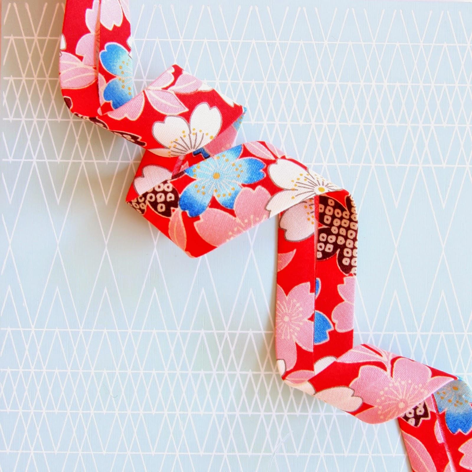 25 mm skråbånd enkeltfoldet i japansk stof med smukt kirsbærblometer motiv.