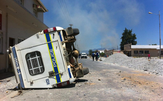 A police vehicle overturned during violent protests in Wolseley