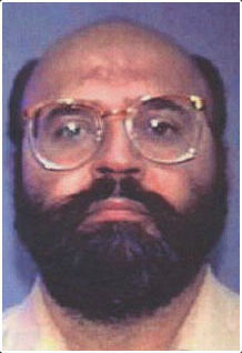 Interpol mug shot of a balding middle-aged man of Indian ethnicity, with a fringe of black hair and a full black beard and mustache. He is wearing large 1980s style eyeglasses.