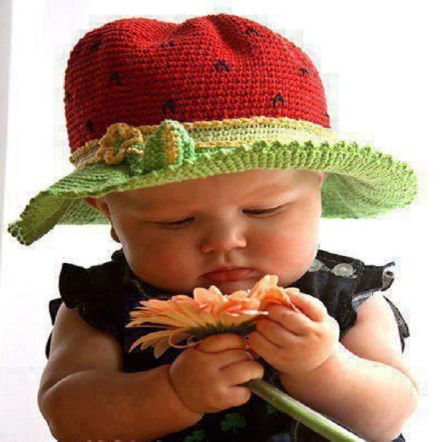 Photo d'un bébé adorable qui tient une joli fleure