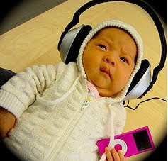This is a baby wearing headphones and listening to her iPod.