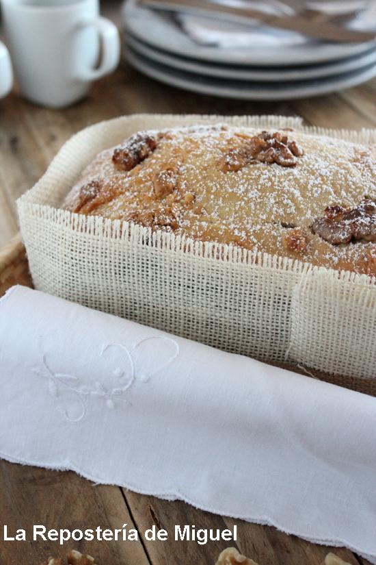 Un pan de platano rodeado con una tela de saco sobre una cesta de mimbre, vista desde un lateral y solo la mitad del pan, se aprecian nueces en su parte superior y azúcar glass espolvoreado sobre ellas.
