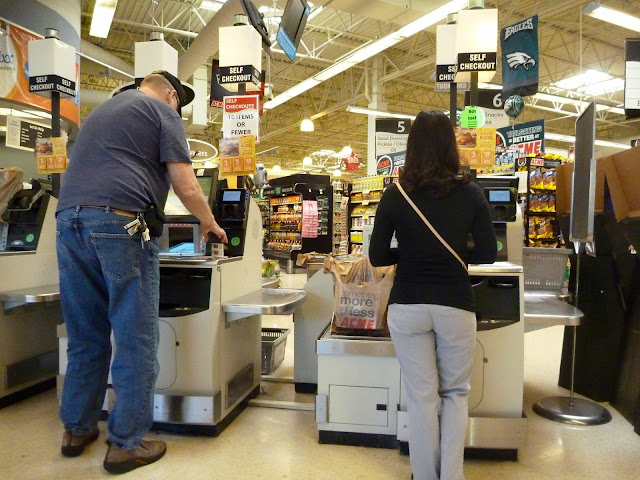 woman and man shopping at grocery store self checkout