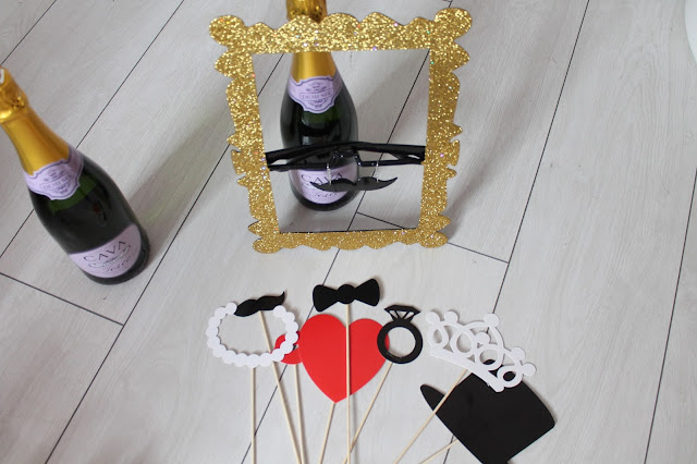 photo booth props and champagne gold glitter frame prop with glasses