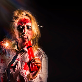 Photo of a female zombie holding lit sticks of dynamite.