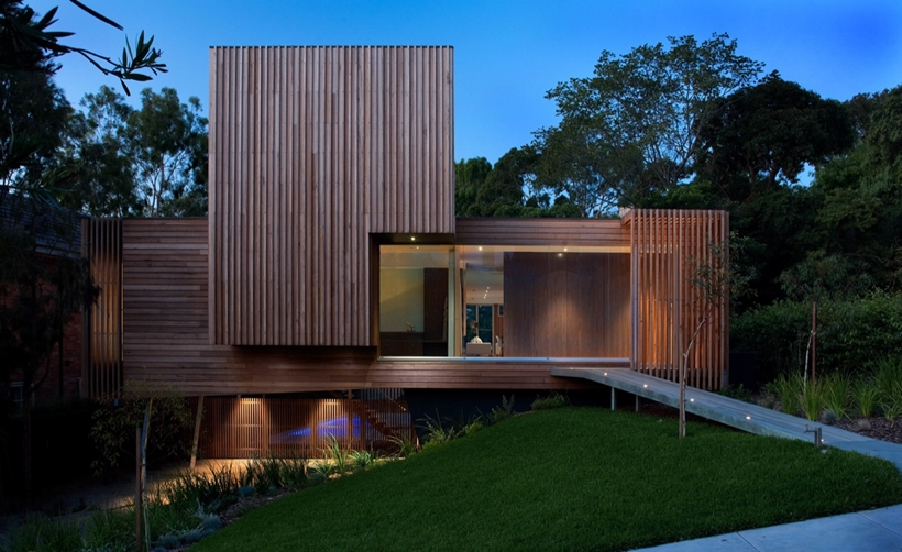 Street facade of Kew House by Vibe Design Group at dusk