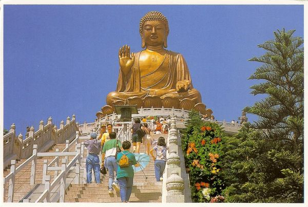 giant bronze statue of Buddha with people climbing steps up to it