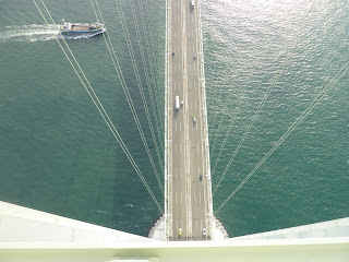 Looking down and the road deck from the top of one of the main towers on the Akashi Kaikyo bridge, There are cables supporting the bridge visible as well as a boat in the sea about to cross underneath the bridge