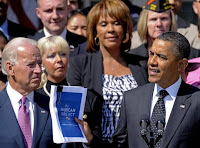 President Obama, accompanied by Vice President Biden and others, holds up a copy of his American Jobs Act during a speech at the White House on Sept. 12, 2011.