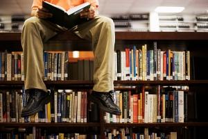 homme assis dans une bibliothèque avec des livres