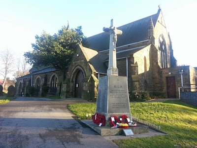 A colour photo of a church and war memorial.  The memorial is a sloping block topped with a calvary cross.  On each side of the block are granite tablets with the names of the men of Cudworth inscribed.  Poppy wreaths surround the bottom of the memorial.