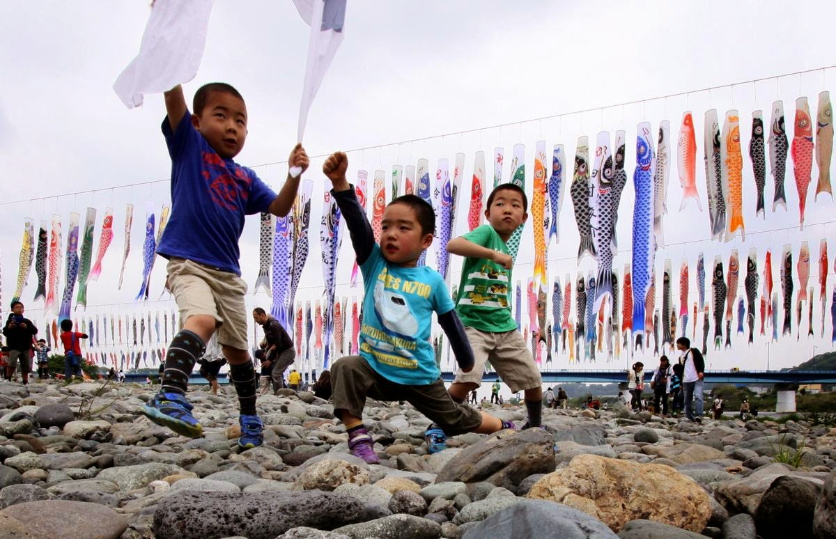 Little boys play under colorful carp streamer
