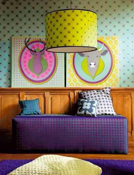Kolorowa tapeta i kolorowe grafiki, żółty abażur i barwne tekstylia