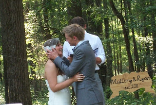 At the outdoor alter, the groom is about to kiss the bride on the forehead. The pastor looks on.