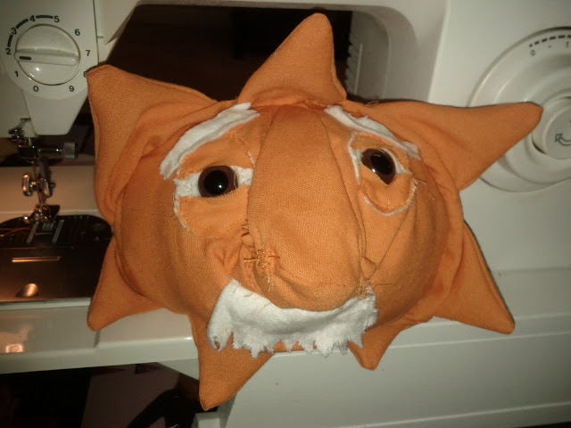 The orange ball now has rays protruding out from it.  The eyes are old looking with brown irises and black pupils.  White eyebrows have been added and the whole character has been stuffed.