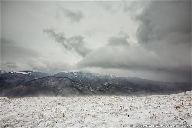 Вот так выглядят горы уже с высоты чуть более 1 тысячи метров. С поземкой на переднем плане. Заметили, снега здесь под ногами немного больше, чем там, внизу? Запомните и эту фразу