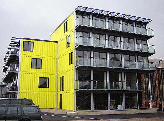 Prédio amarelo de quatro andares construído de contêiners reciclados