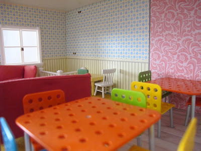 Interior of the ground floor of a half-built Lundby dolls' house, with tables and chairs.