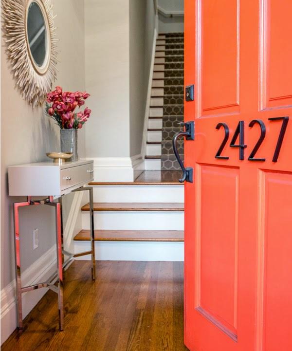 puerta de entrada de color naranja consola blanca y espejo sol blanco