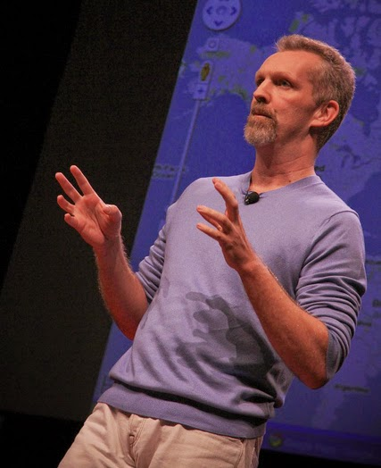 Digital map innovator Lars Rasmussen gives a lecture in front of a blue presentation screen.