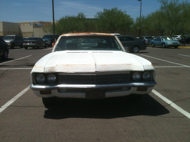 Front view of white 1970 Chevrolet Bel Air with rusty roof parked in parking lot