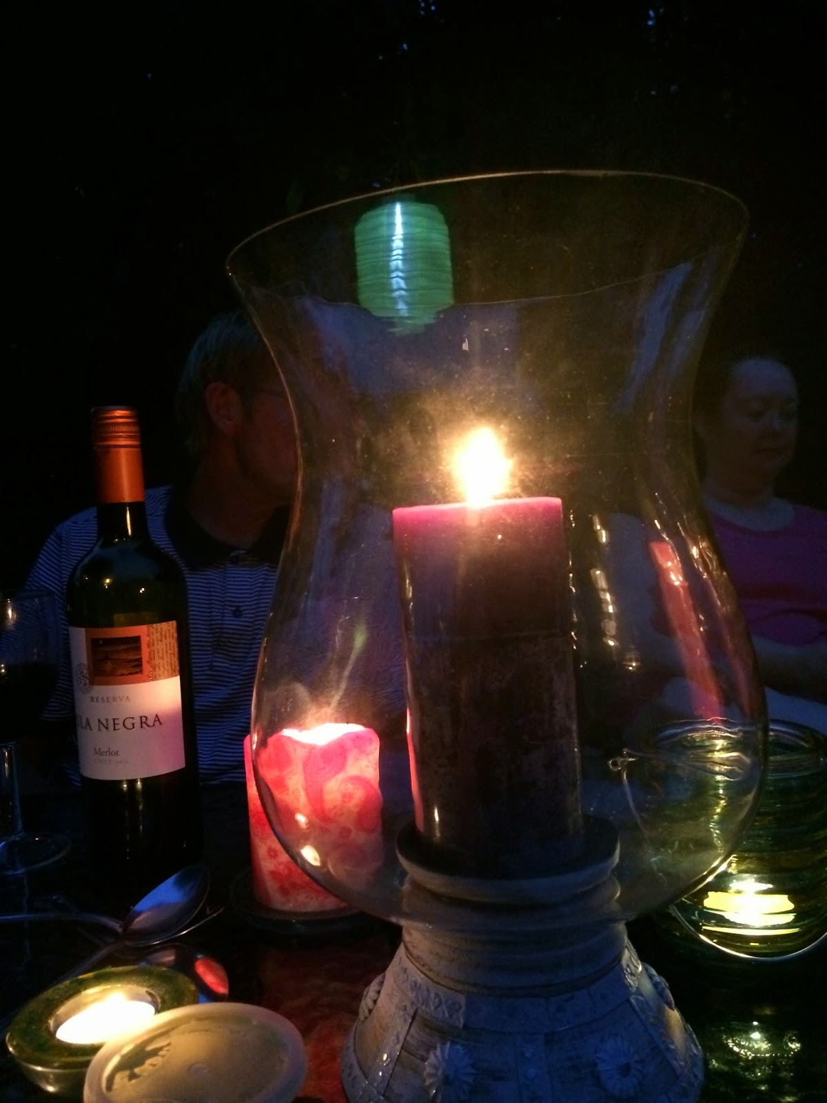 lantern on table with candles and wine bottle