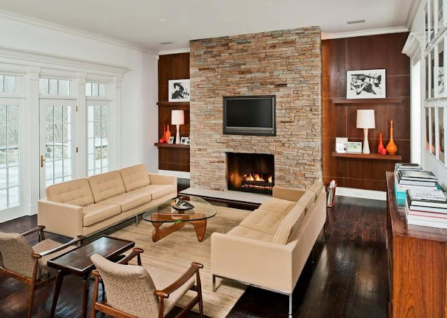 Den in a mansion with a mid century modern vibe with a stone fireplace, a Noguchi coffee table, dueling sofas, and a wall mounted TV