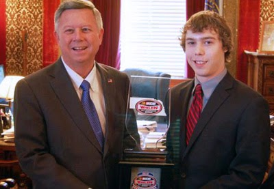 Nebraska Gov. Dave Heineman and NASCAR Whelen All-American Series state champion Jase Kaser with the 2013 NASCAR championship trophy.