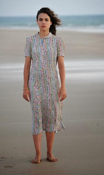 Sira Quiroga playa vestido de flores con fondo blanco. El tiempo entre costuras. Capítulo 1.