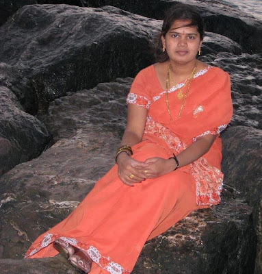 Homely looking aunt taking rest at beach shores.