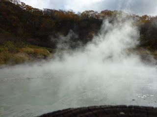 Sulfurous pond near noboribetsu-onsen's Jigokudani (Hell valley) emitting a lot of steam with a bit of hill and trees in background