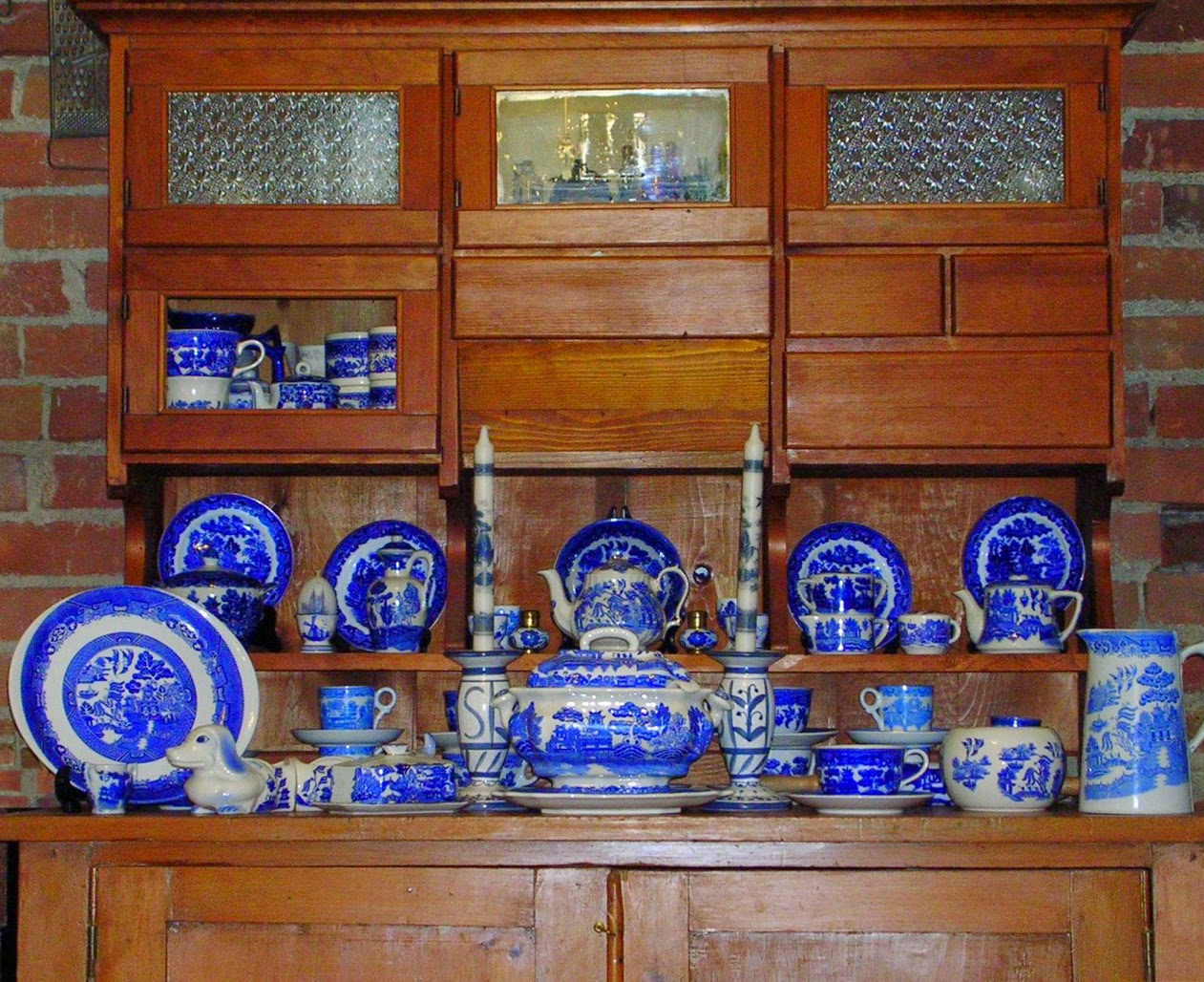 A display of vintage blue willow china in an antique kitchen cabinet.
