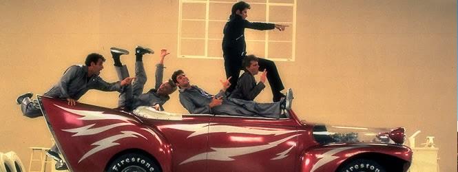 John Travolta e elenco na performance de Grease Lightning.