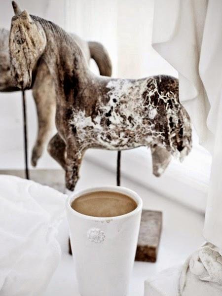 Drewniana rzeźba konia i kawa w kubku