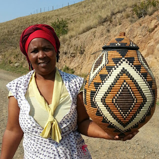 Ukhamba weaver and her basket with traditional diamond and stair step designs.