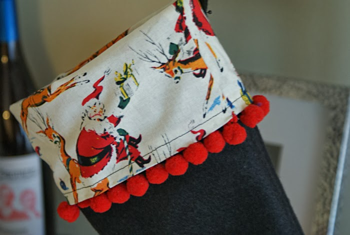 christmas stockings with red pom poms and vintage inspired fabric