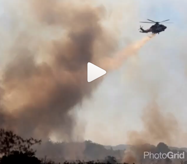 Photo of LAFD helicopter making a water drop on brush fire.