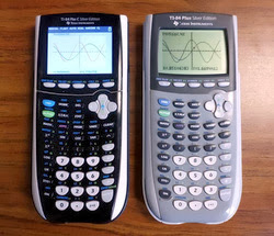 Two graphing calculators sitting on a table next to each other. One is black and one is grey. They both have functions graphed on the calculator screen.
