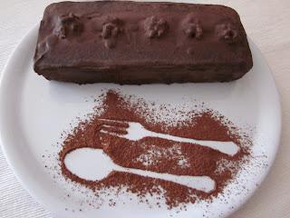 Foto panorámica de brownie en plato blanco. Dentro del plato con cacao han espolvoreado una cucharilla y un tenedor junto al brownie dentro del plato.