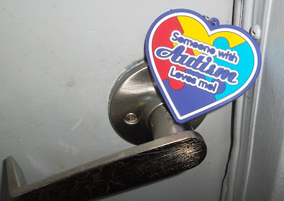 Heart keychain divided into four interlocking quadrants on the diagonal that in clockwise order from top, are colored yellow, light blue, dark blue or purple and red. A caption printed on the keychain reads, 'Someone with Autism Loves Me!' The keychain is balanced on a door handle, braced against the frame of the door.