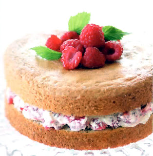 Raspberry and Hazelnut Gateau classic layer cake leavened with beaten eggs that's sandwiched with a cream and raspberry mix and decorated with fresh raspberries