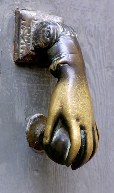 Türklopfer aus Messing, Türklopfer als Hand an einer Holztür in der Provence, Frankreich