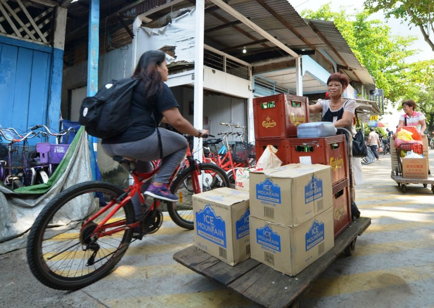 Ms Goh Lai Guat (far right), 60, and her sister pushing trolleys of supplies and bottled water to their food stall on Pulau Ubin after an advisory from the authorities on the usage of well water.
