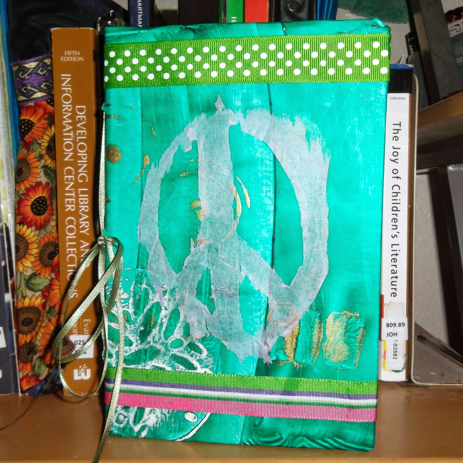 Handmade book, stood-up with front cover forward. Visible behind it are the spines of shelved books.