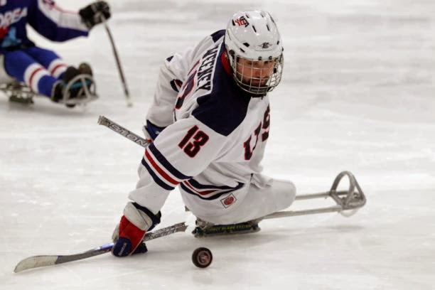 picture of josh sweeney on  the ice playing sled hockey with the puck and two shorter hockey sticks
