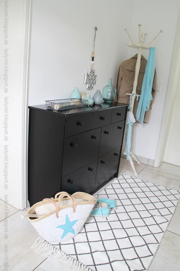 schwarze Kommode mit türkisblauer Deko, weißschwarz karierter Teppich, im Vordergrund eine Korbtasche und Chucks