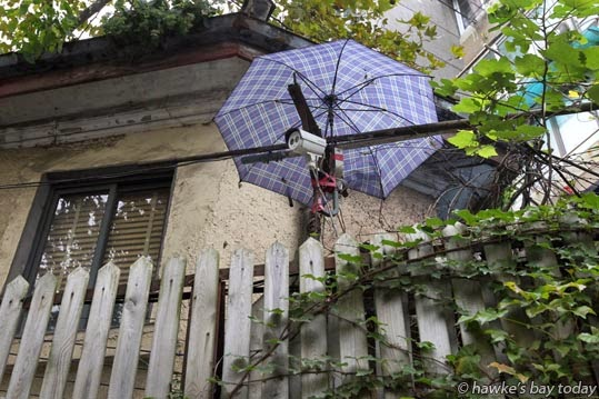 Security camera protected from the weather by an umbrella photograph