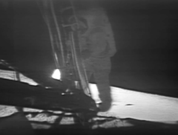 Armstrong taking his first step onto the surface of the moon.