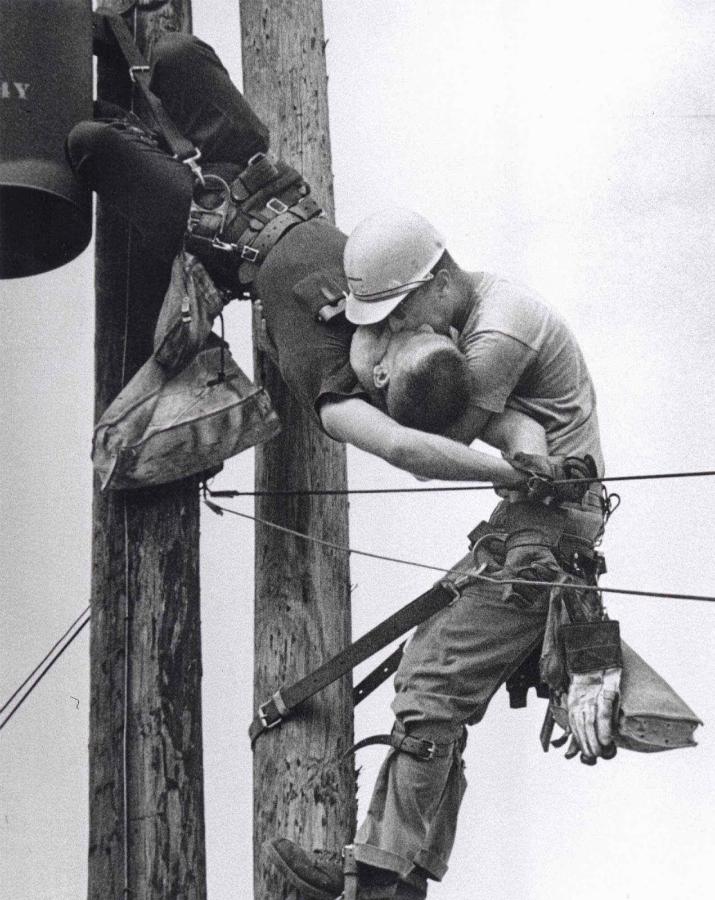 dos hombres besándose en un poste de alta tensión